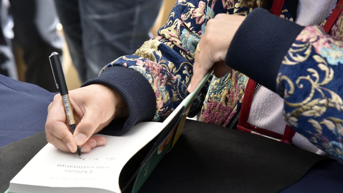 Una escritora firma un libro en Barcelona durante la festividad de Sant Jordi.