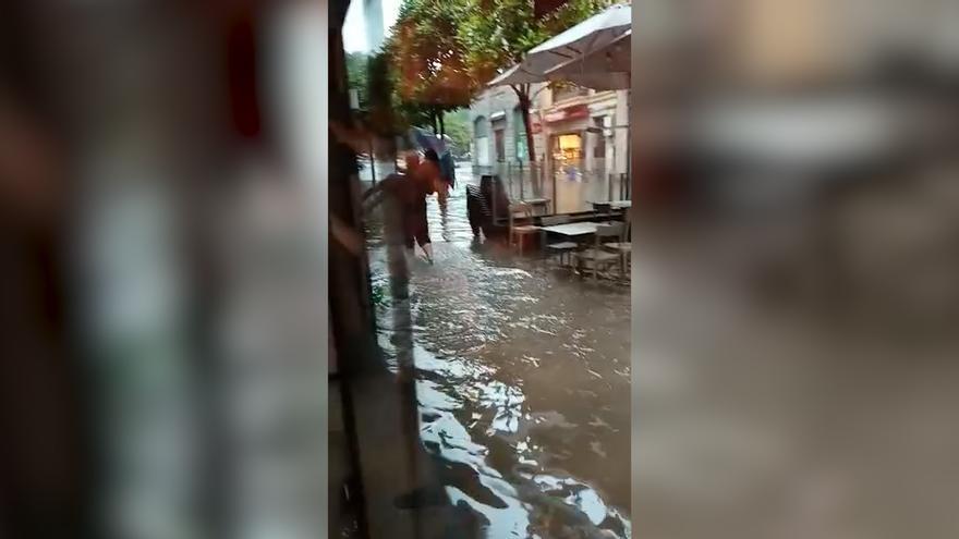 La tromba de agua de Oviedo inunda las terrazas y corta el paso en las calles del centro
