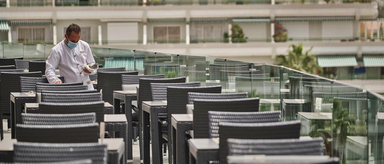 Un camarero prepara mesas para la comida en una terraza vacía en el sur de Tenerife.