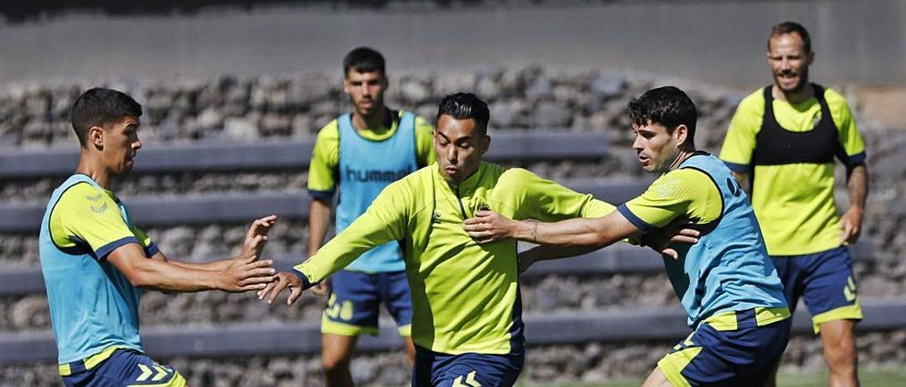 Sergio Araujo –centro– lucha por el balón con Cardona –izquierda– y Sergio Ruiz –derecha– en el entrenamiento de ayer. |