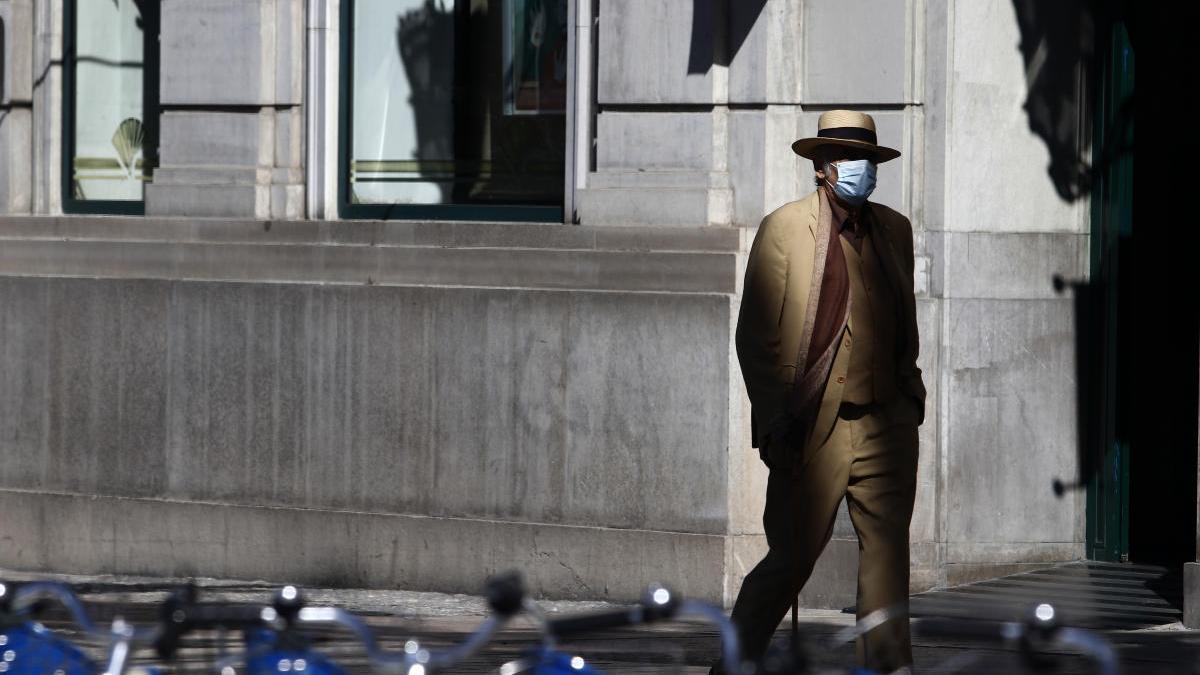 Un hombre camina por una calle del Centro de Málaga, rotegido por una mascarilla