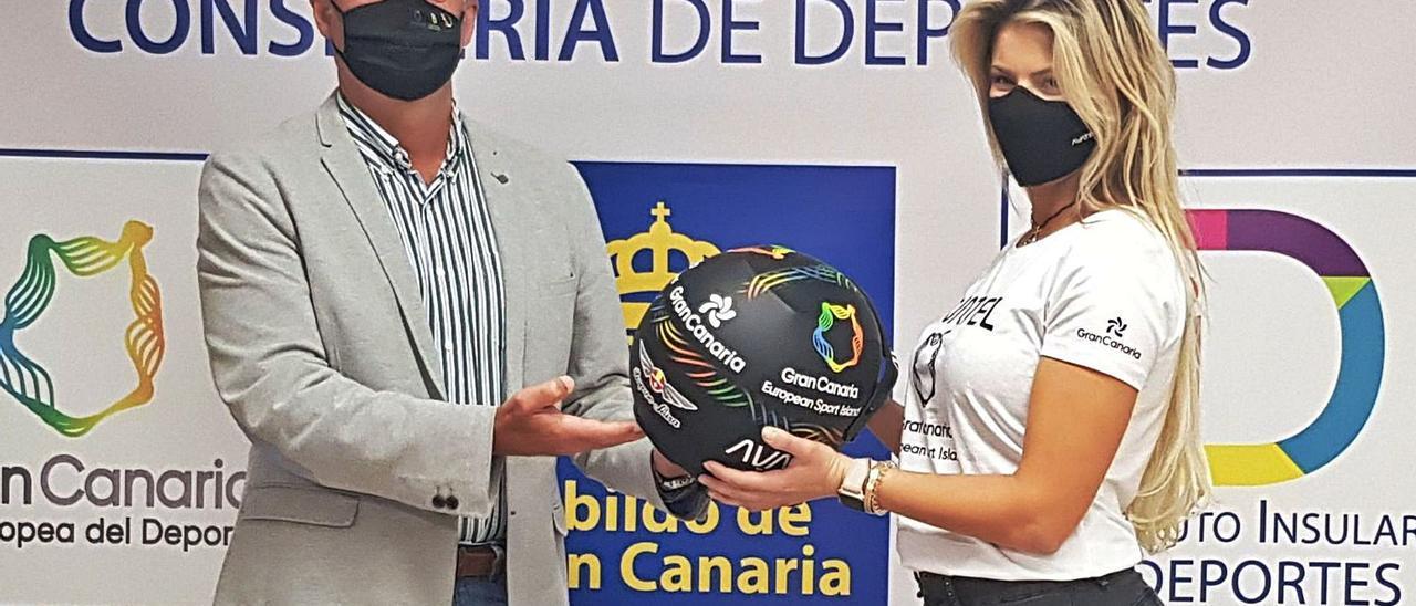 Christine Giampoli y Francisco Castellano sujetan el casco de la piloto, en el que aparece la imagen de Gran Canaria, durante la presentación de ayer. | | LP/DLP