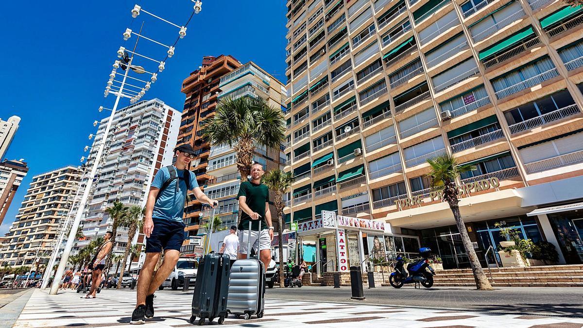 Turistas llevan sus maletas en la playa de Levante de Benidorm, plagada de apartamentos turísticos, en una imagen de hace dos veranos.  