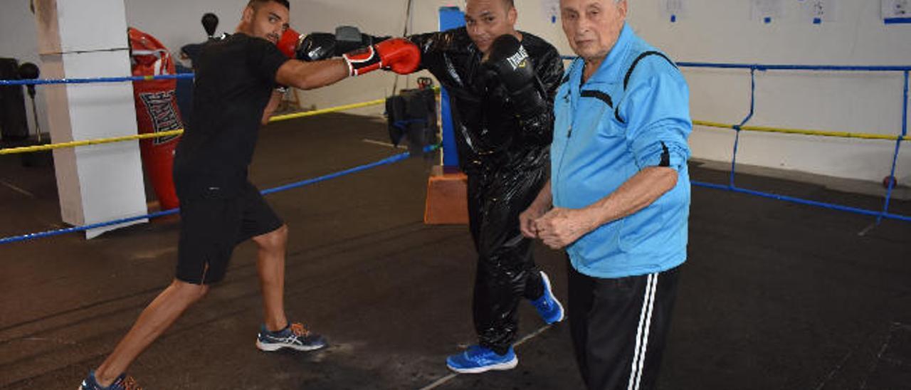 Manuel Santacruz 'Palenke', en el ring de su escuela de boxeo, junto a sus alumnos 'El príncipe gitano' (i) y 'Doblecara'.