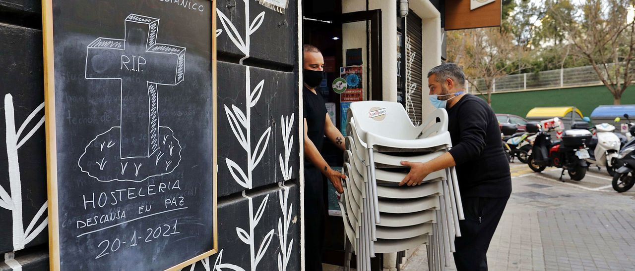 Dos trabajadores recogen  ante un cartel de protesta  por el cierre.  M A Montesinos | M. A. MONTESINOS