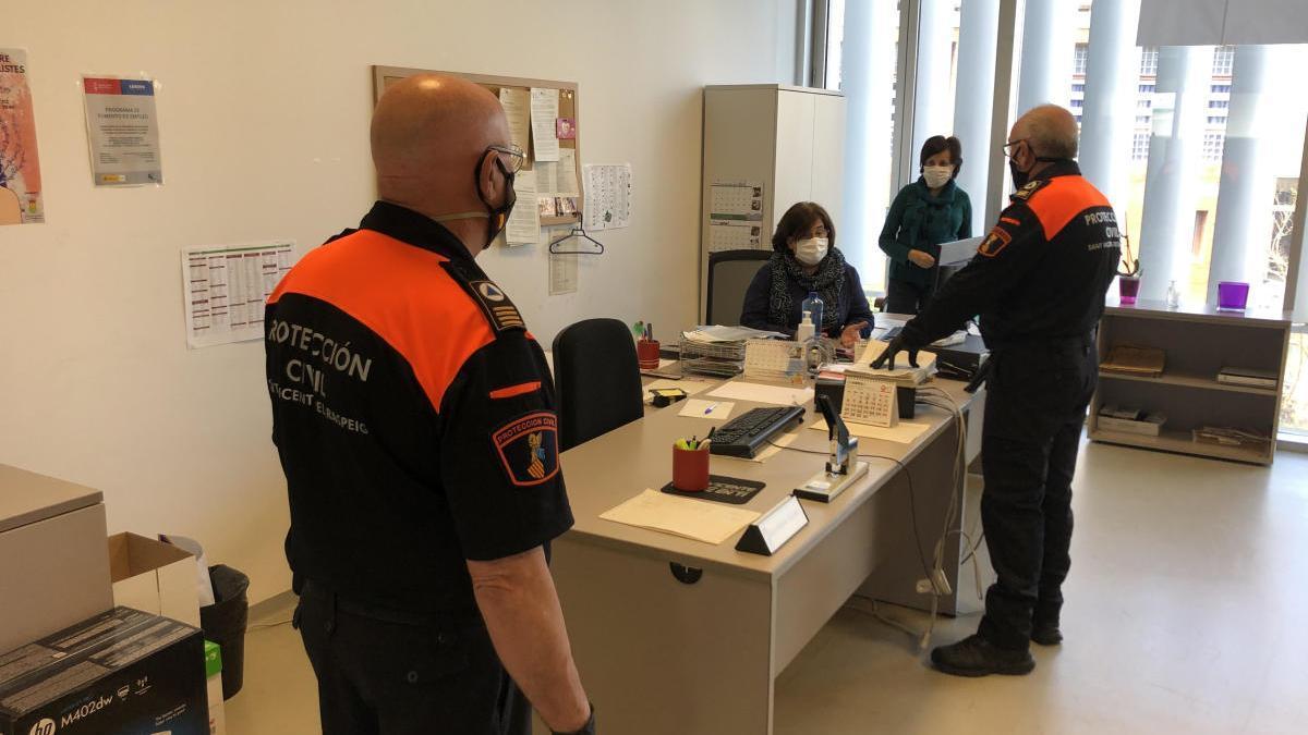 Voluntarios de Protección Civil recogen los cheques para iniciar su reparto.