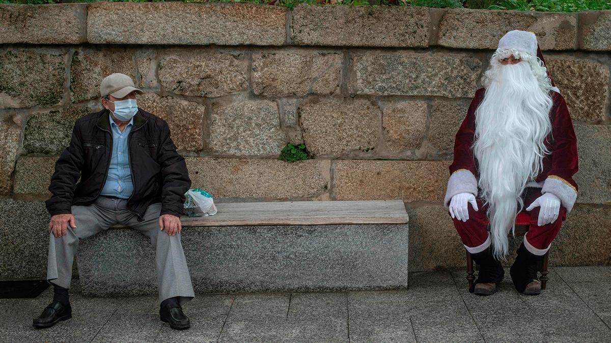Papá Noel descansa junto un ciudadano con mascarilla en la víspera de Nochebuena