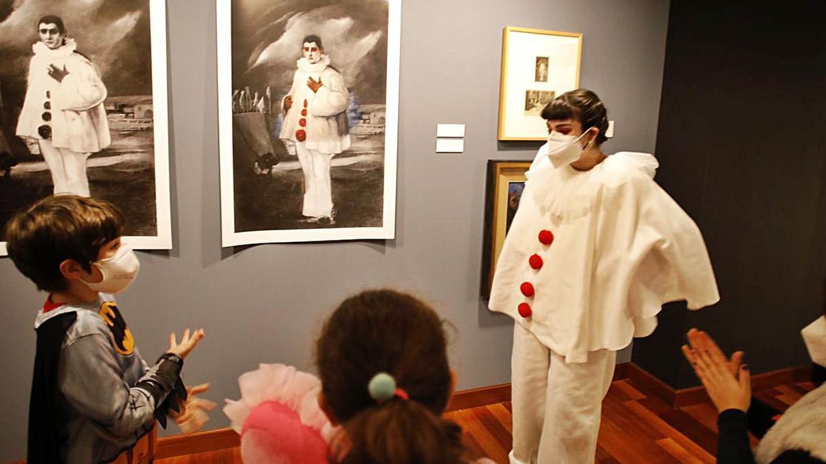 La estudiante Carmen Estrada enseña a varios niños el retrato que Evaristo Valle hizo de  Pierrot. | Ángel González