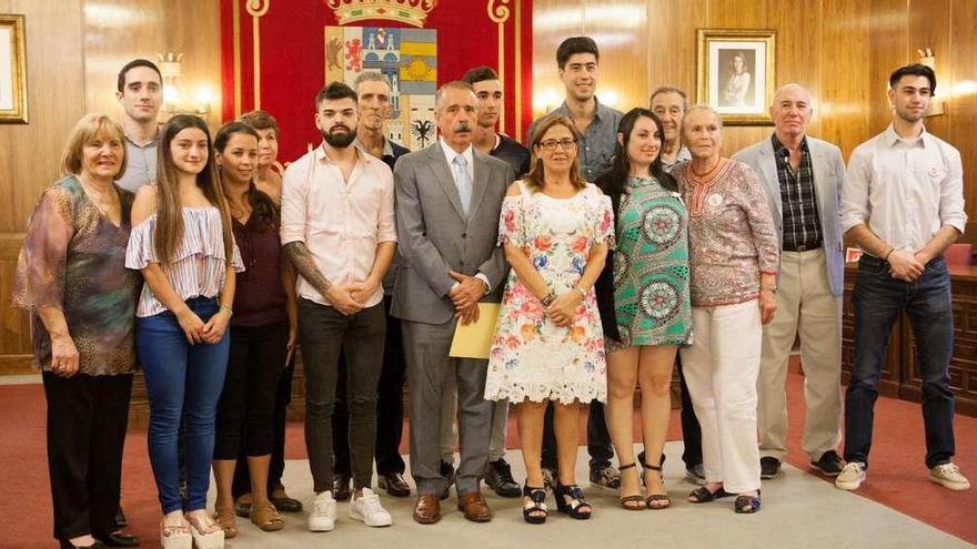 Los catorce participantes de los programas Añoranza y Raíces posan junto a Mayte Martín Pozo y José Luis Bermúdez, ayer en la Diputación.