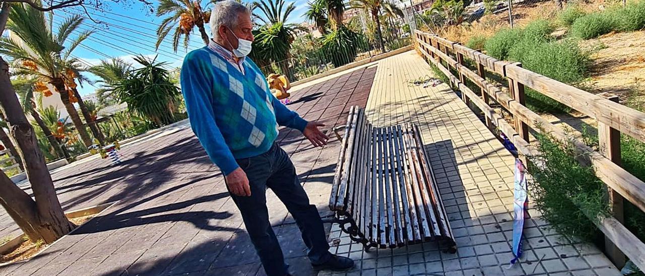 El representante vecinal de Portes Encarnades señalando un banco roto en el parque Veleta.