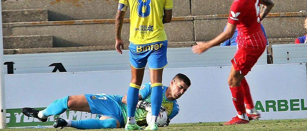 El portero Raúl Fernández atrapa el balón ante la presencia de su compañero Maikel y del sevillista Ocampos.