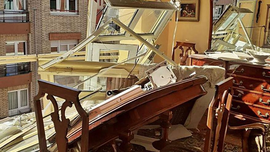 El espectacular derrumbe de una cornisa en la calle Luanco destroza dos coches