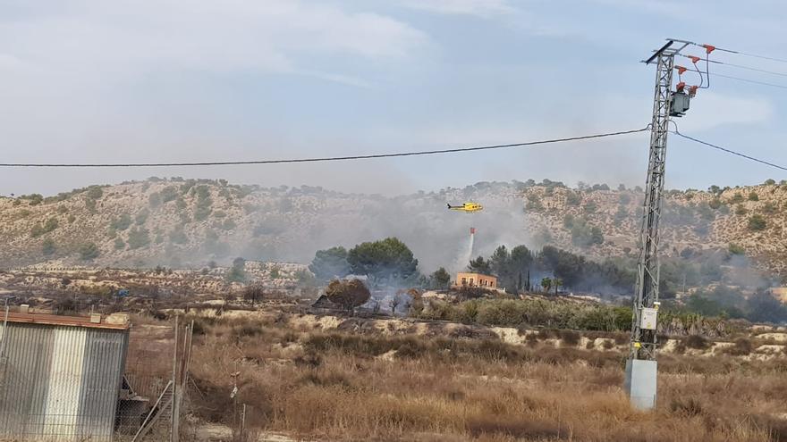 Los bomberos atajan un incendio en una finca con pinar y viviendas junto al embalse de La Pedrera en Torremendo