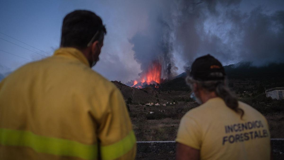 Un grupo de extinción de incendios observa una de las bocas del volcán.