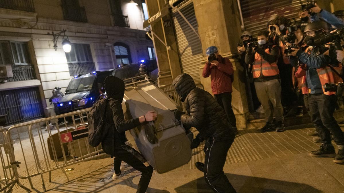 Manifestantes tratan de lanzar un contenedor en las protestas de Barcelona.