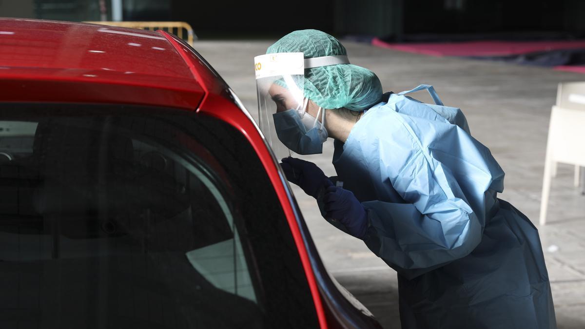 Una sanitaria atiende a un avilesino en el autocovid de La Magdalena.