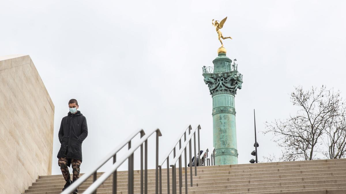 Un joven con mascarilla en la plaza de la Bastilla de París