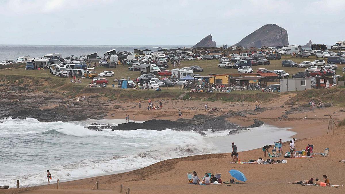 La playa de Verdicio y el aparcamiento que desde hace años se llena de furgonetas y autocaravanas, el pasado mes de junio.   Mara Villamuza