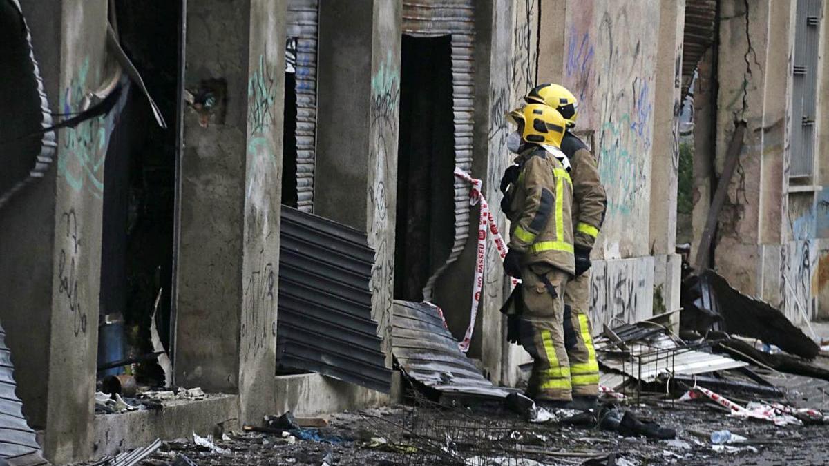 Dos bombers miren dins la nau incendiada del barri del Gorg de Badalona