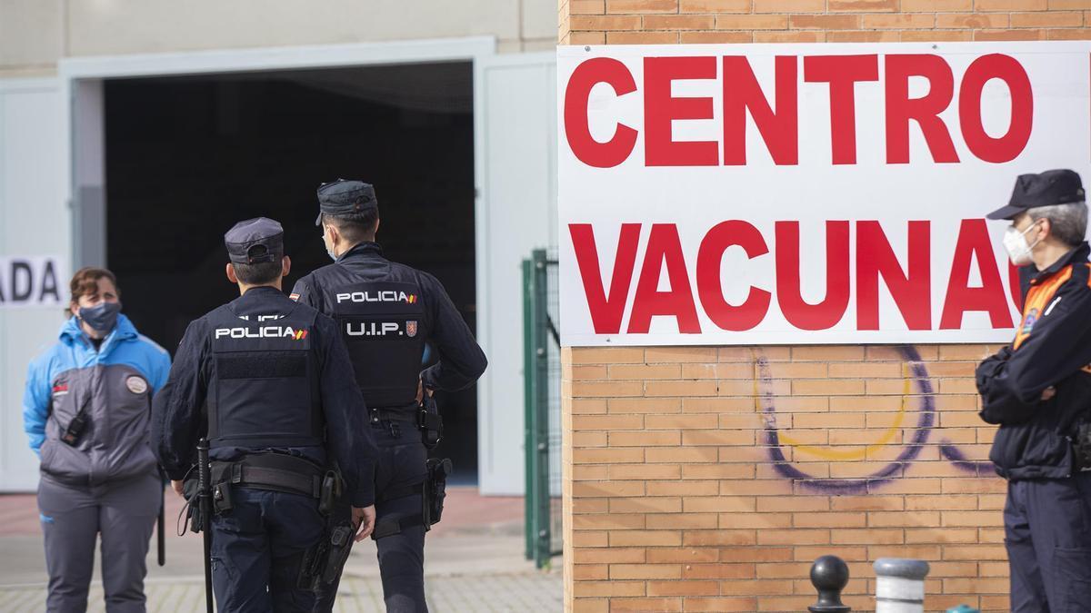 Policía en una cola para vacunarse.