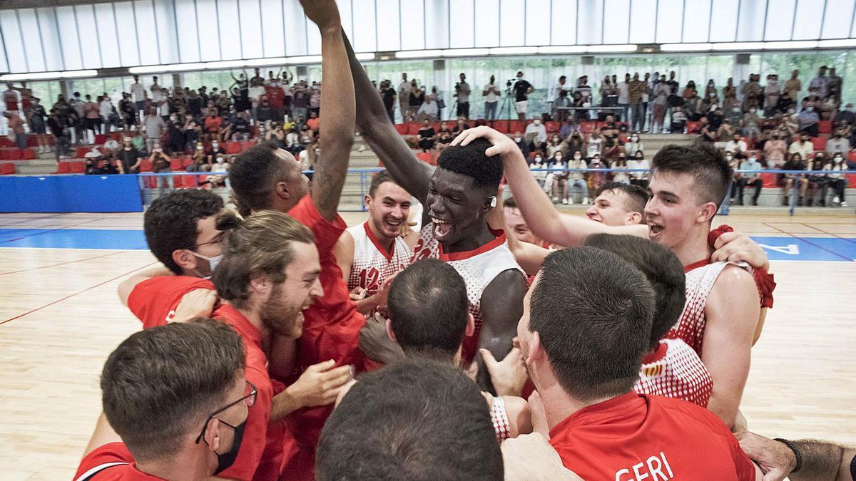 Els jugadors del CB Navàs Viscola feliciten Serigne Fallou, jugador clau ahir, amb el públic aplaudint al fons, a la graderia | OSCAR BAYONA