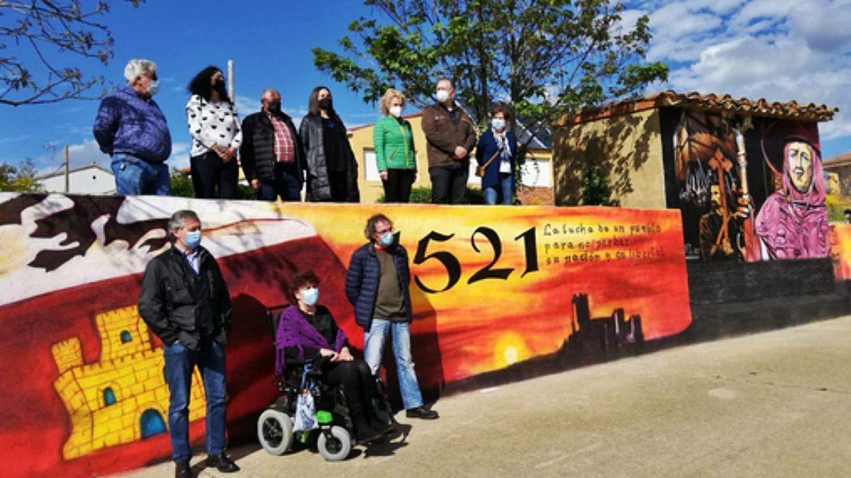 Las autoridades asistentes al acto y el autor del mural posan junto al mural.