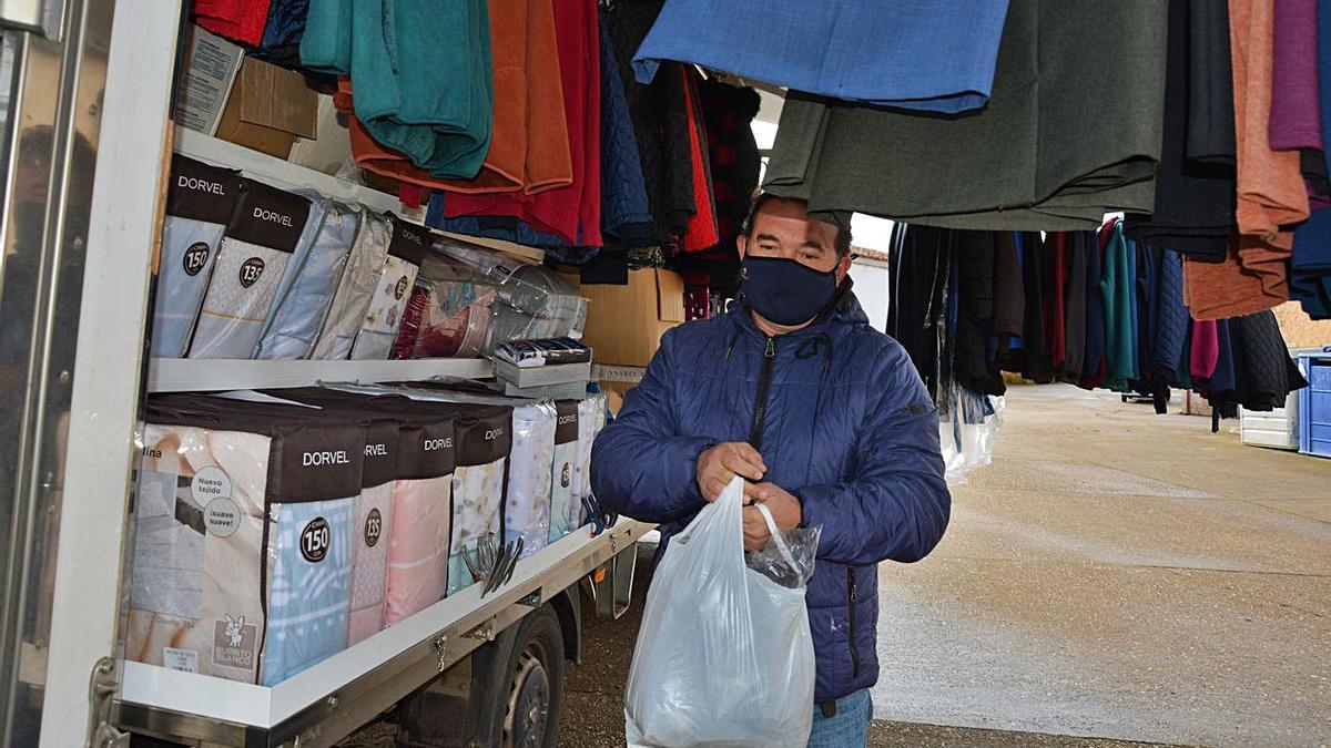 José Miguel Caballero entrega una bolsa con ropa que acaba de vender en su puesto ambulante. | Araceli Saavedra