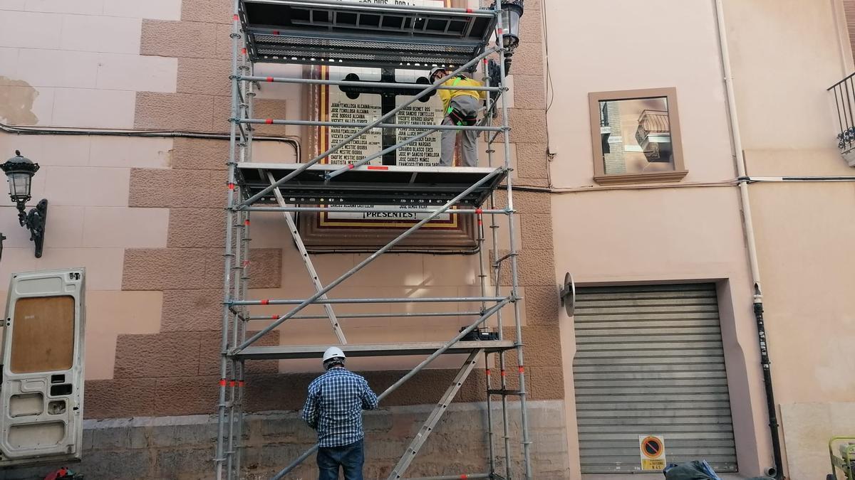 Operaris instal·len la bastida per a retirar el mural