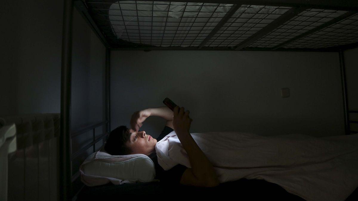 Un adolescente consulta su teléfono móvil en el dormitorio.