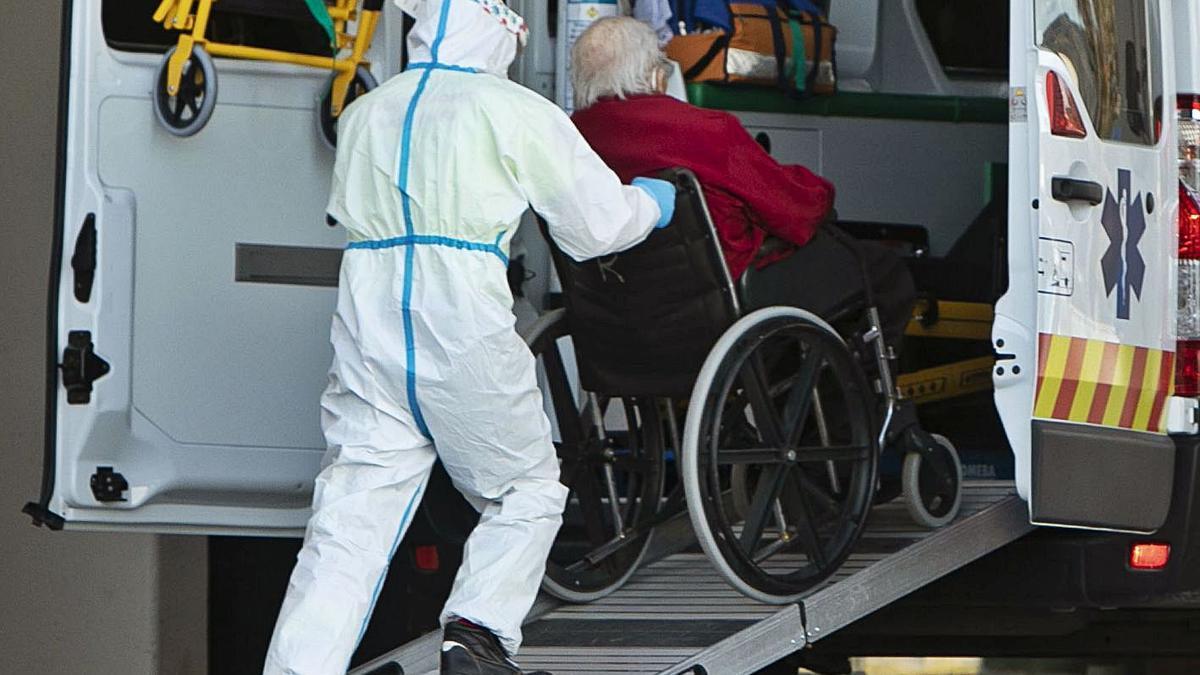 Un sanitari, amb un equip de protecció,  baixa un malalt d'una ambulància.   DANIEL TORTAJADA M.