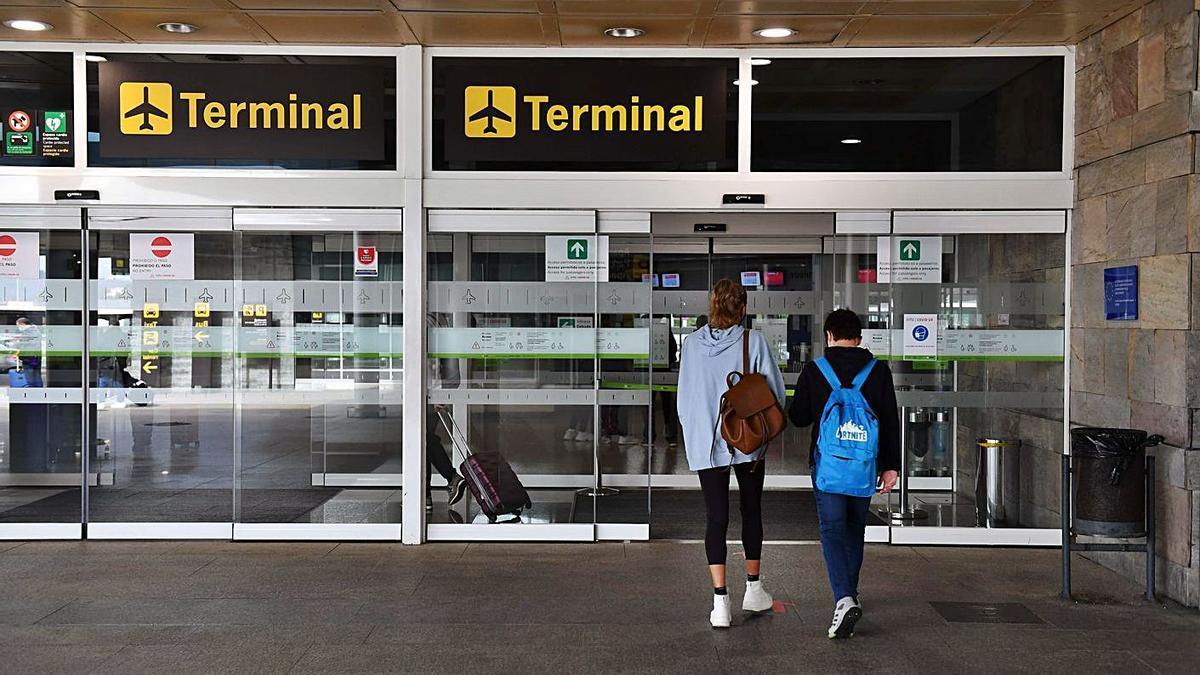 Pasajeros a la entrada de la terminal del aeropuerto de Alvedro.     // VÍCTOR ECHAVE