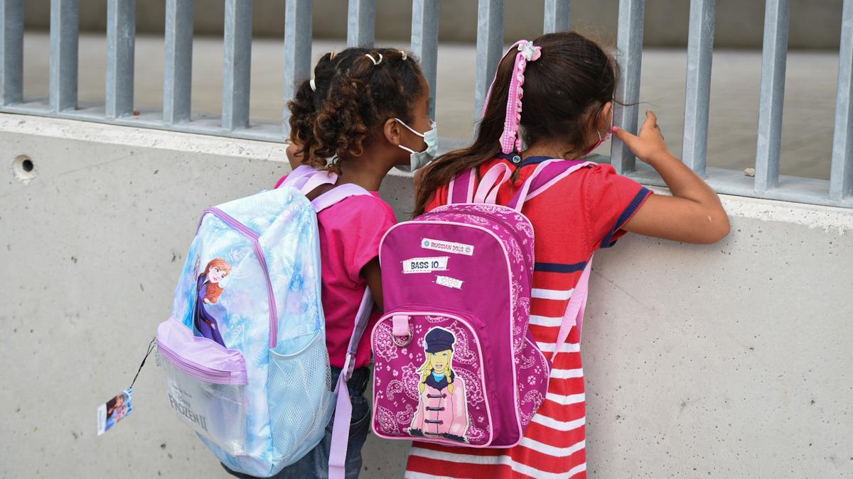 Dos niñas a las puertas de un colegio.
