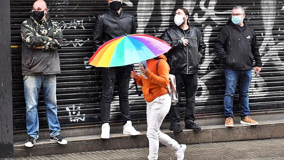 Varias personas se protegen de la lluvia.     // VÍCTOR ECHAVE