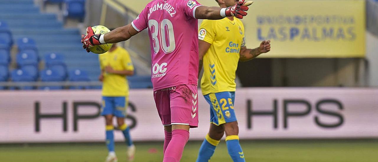 El portero Álex Domínguez, con el balón mientras Aythami pasa por delante suyo durante el choque del lunes.     ANDRÉS CRUZ