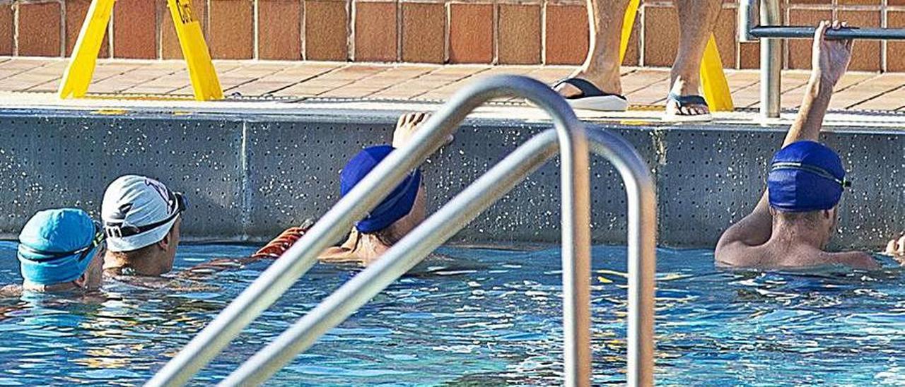 Jóvenes nadando en una piscina municipal, este mes. | ALEX DOMÍNGUEZ