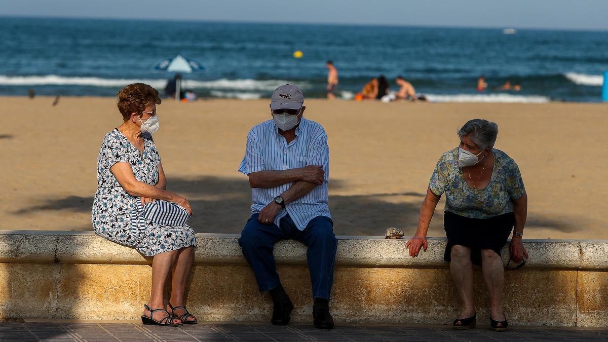 Tres personas mayores descansan en el paseo marítimo de la playa de la Malvarrosa.