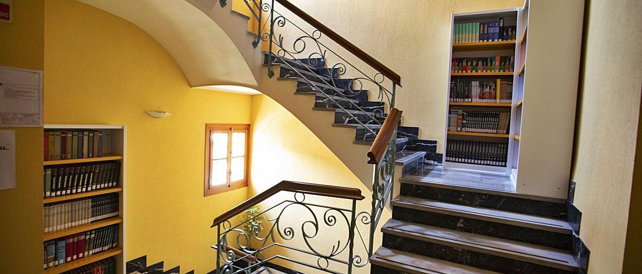 Estanterías en las escaleras de acceso a la biblioteca de Xàtiva, en una imagen de ayer. | PERALES IBORRA