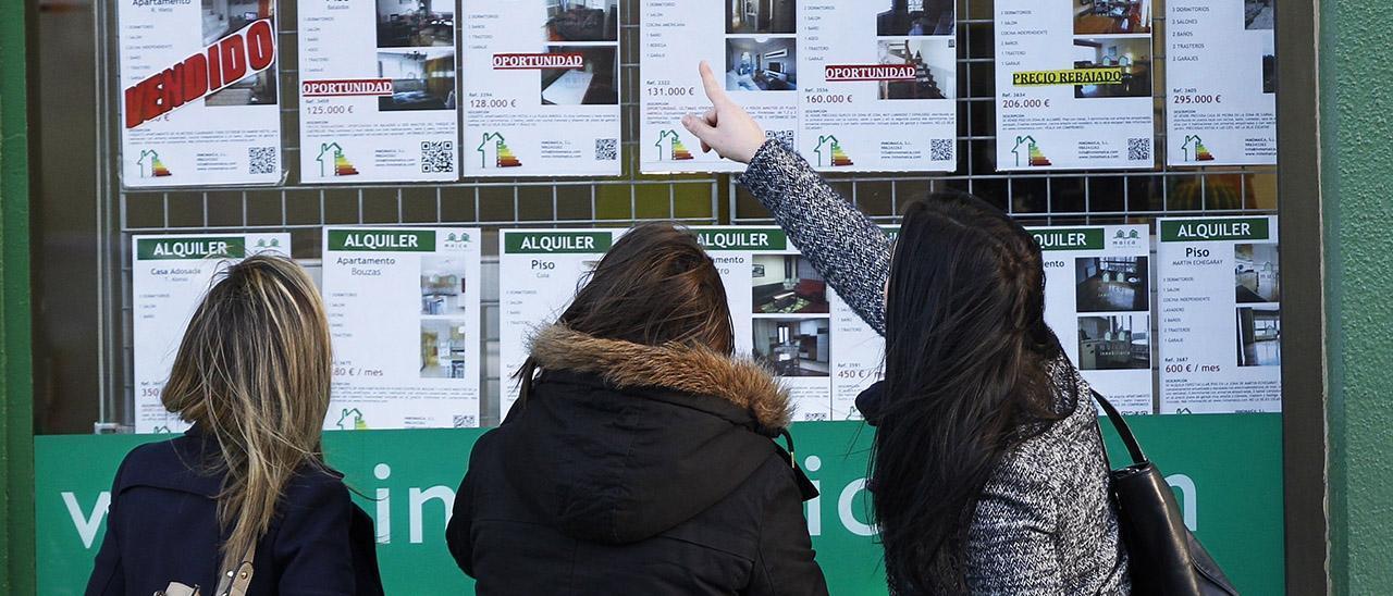 Tres jóvenes observan precios en una inmobiliaria