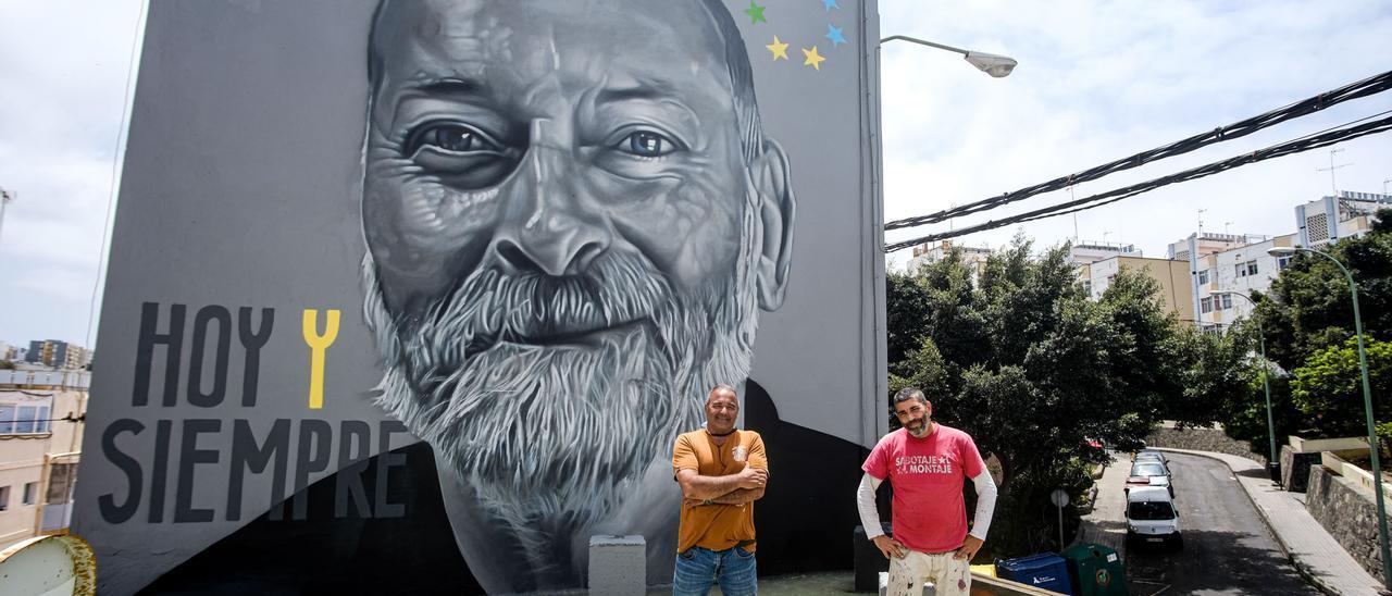 Toni Farías (dcha.) y el autor del mural, Sabotaje al Montaje (izq.), junto al mural casi terminado en honor a José Puche