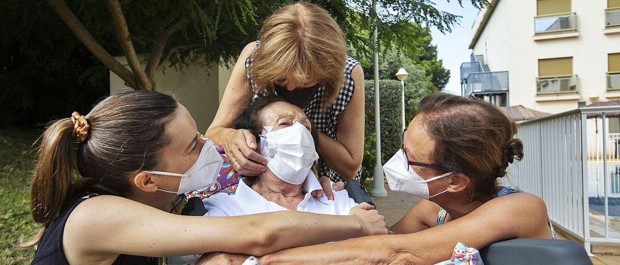 Una anciana de una residencia de Alicante recibe los abrazos de dos de sus hijas y de su nieta en el primer día del nuevo protocolo que rige para estos centros.  