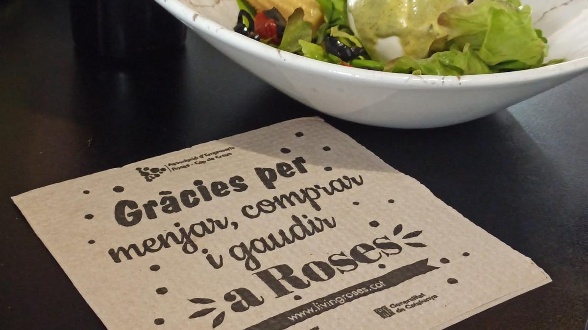 """Tovallons de paper serigrafiats amb el lema """"Gràcies per comprar, menjar i gaudir a Roses"""""""