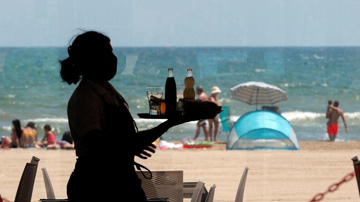 Una camarera lleva bandeja con bebidas en un restaurante de la Malvarrosa.