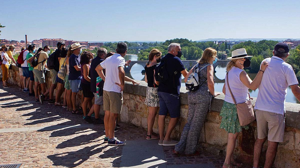 Un grupo de turistas contempla el río Duero desde el mirador del Troncoso.