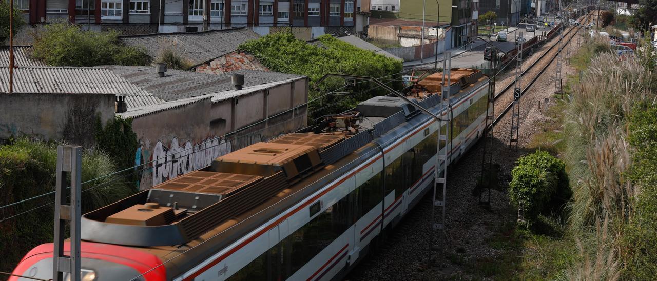 Un tren de Renfe, a su paso por el centro de Avilés.