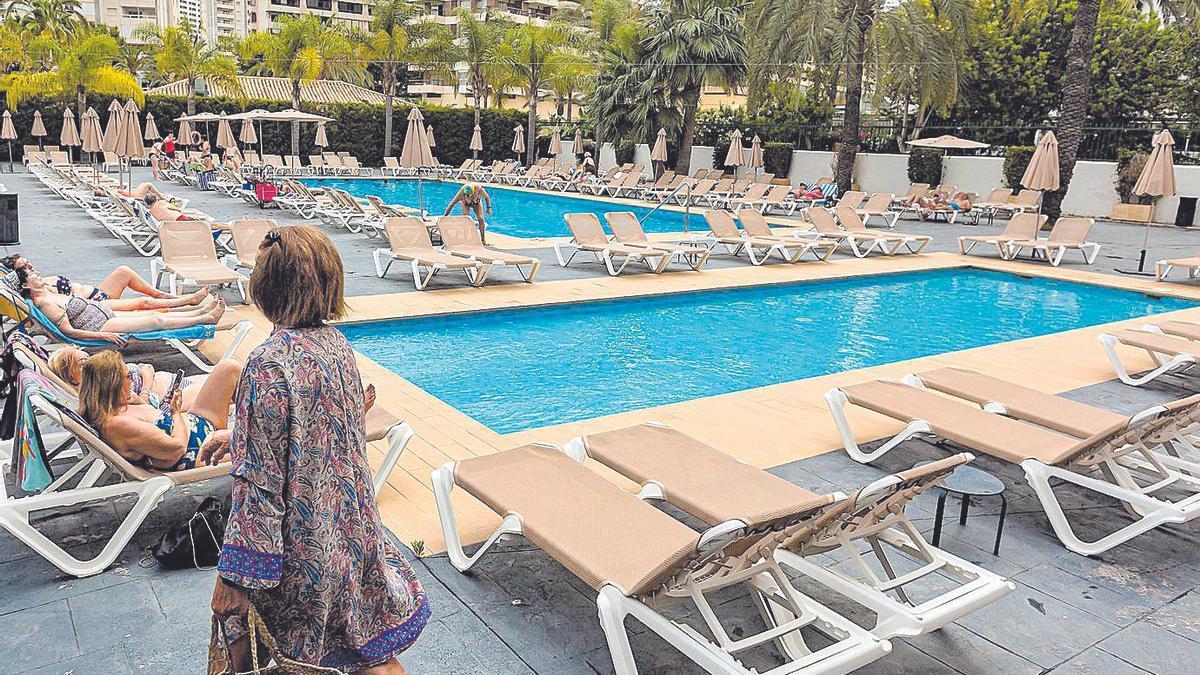 Una mujer se dirige a la piscina de un hotel.