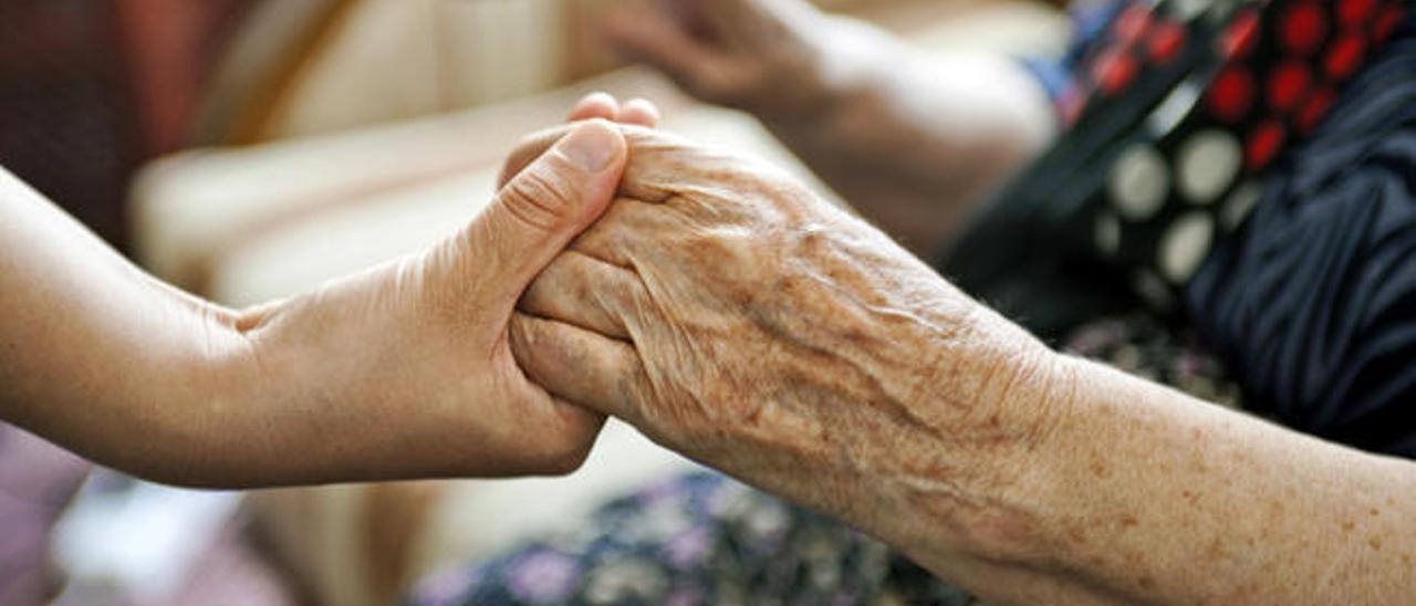 Una mujer sostiene las manos a una anciana.