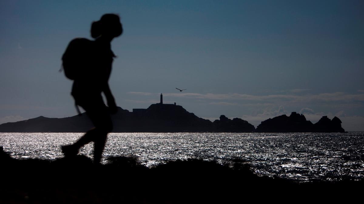 Una mujer camina cerca de la costa.