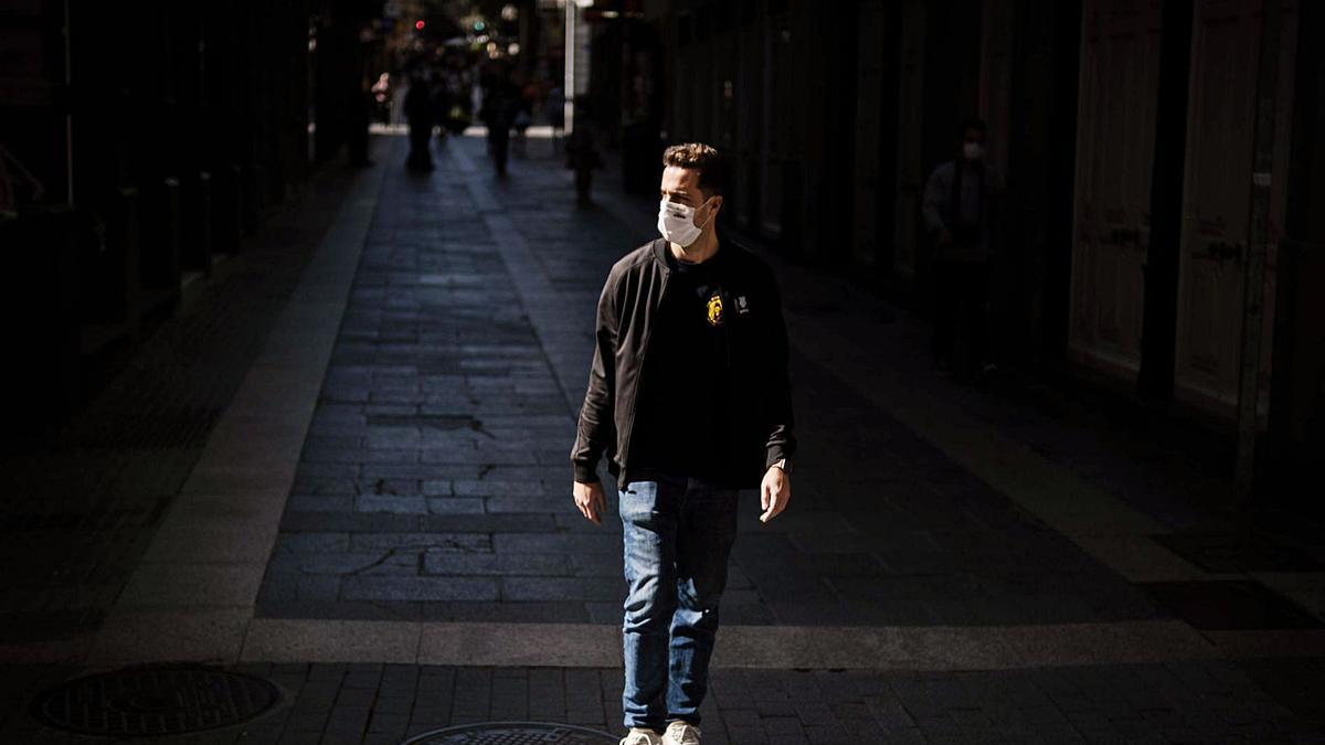 Un joven con mascarilla transita por una céntrica calle de la capital tinerfeña.