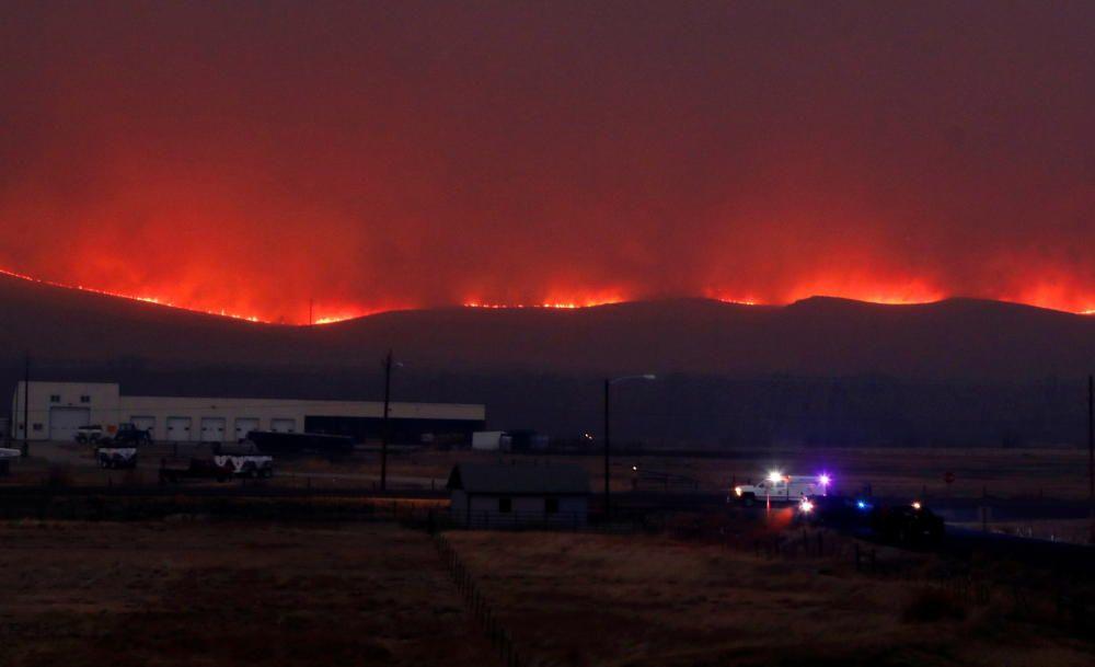 Flames illuminate the sky as the East ...