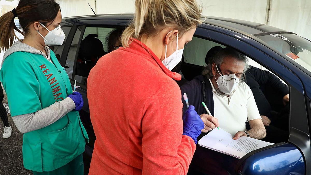 Luis Manuel del Valle, firmando la declaración responsable antes de recibir su primera dosis de la vacuna, en el aparcamiento del rastro de Gijón habilitado como punto de vacunación contra el covid-19.